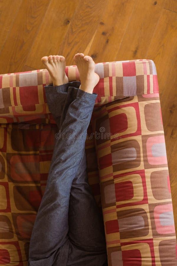Equipa os pés no sofá fotos de stock