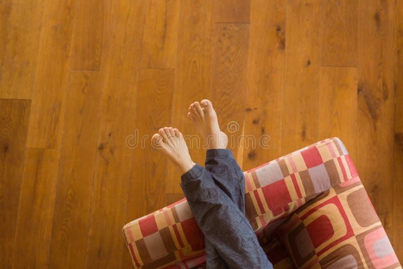 Equipa os pés no sofá imagens de stock