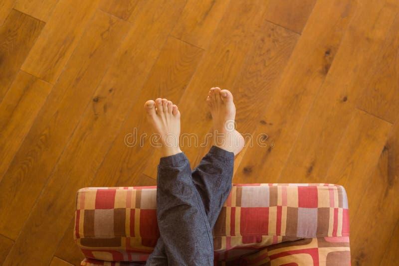 Equipa os pés no sofá imagens de stock royalty free