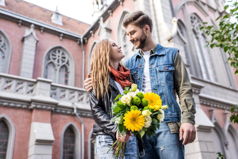 equipaggi abbracciare l'amica con il mazzo dei fiori in mani immagine stock libera da diritti
