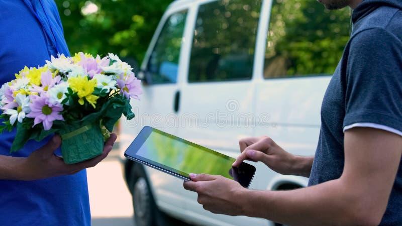Equipaggi aggiungere la firma sulla compressa e la ricezione del fiore presente dal fattorino immagine stock libera da diritti