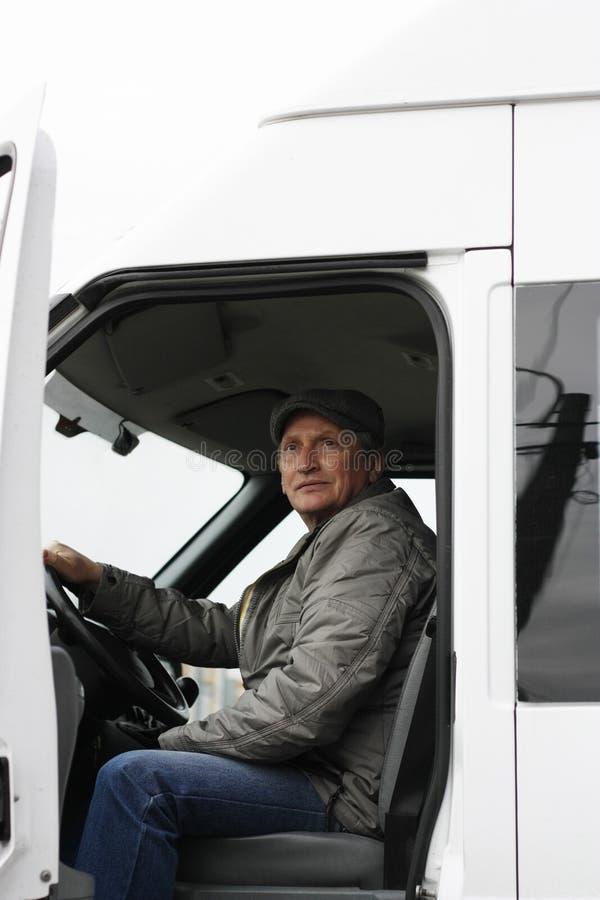 Equipaggi 50 anni dietro il volante dell'automobile bianca fotografie stock