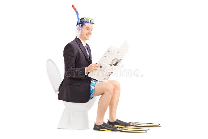 Equipaggi con la presa d'aria che legge le notizie su una toilette immagini stock libere da diritti