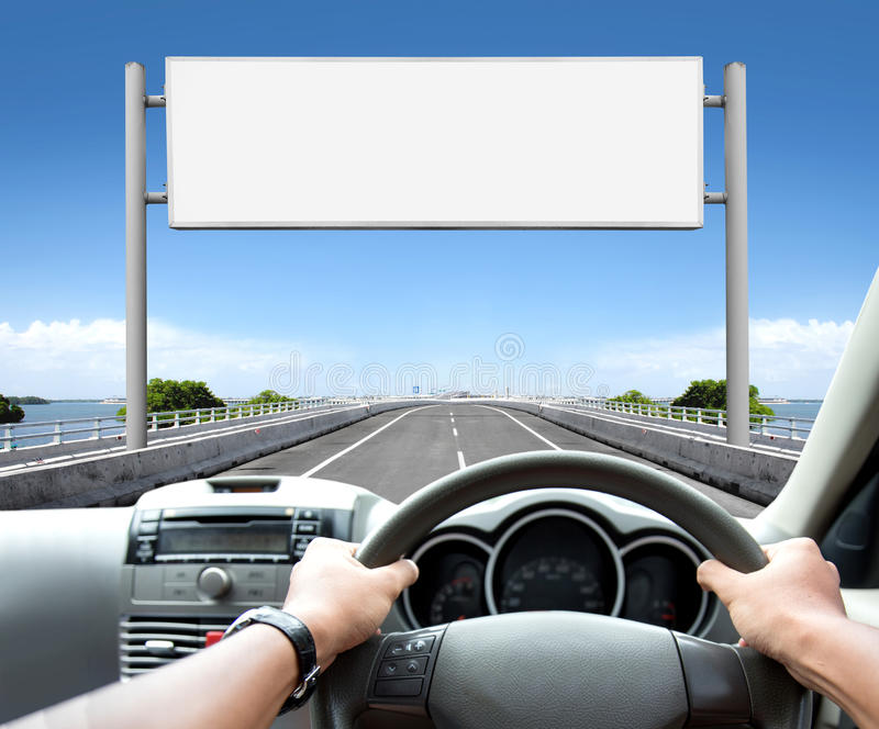 Equipaggi condurre l'automobile sul segno del tabellone per le affissioni e della strada avanti immagini stock