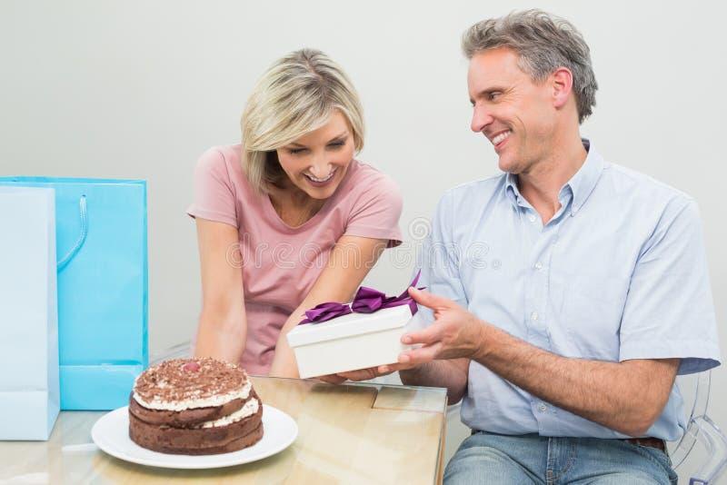 Equipaggi dare ad una donna felice un regalo di compleanno accanto al dolce fotografia stock