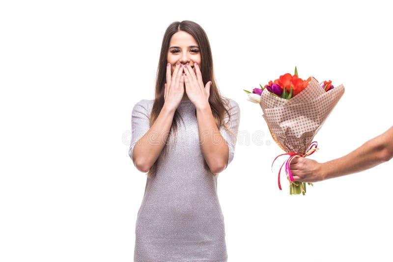 Equipaggi dare un mazzo dei fiori e della donna sorpresa isolati su fondo bianco fotografia stock