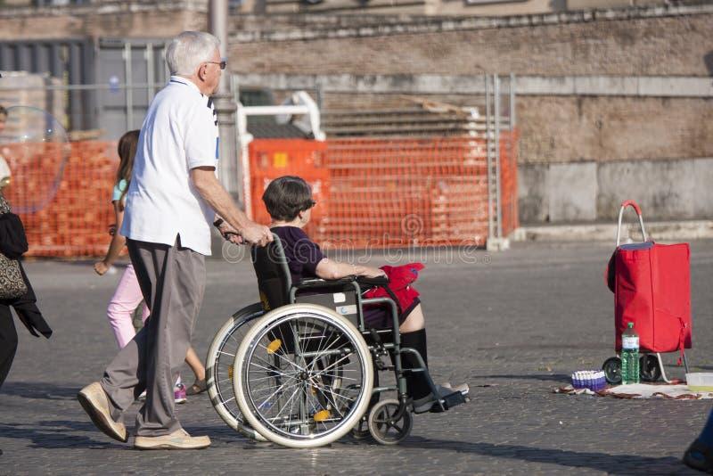 Equipaggi e la sua moglie disabile nella sedia a rotelle fotografia stock