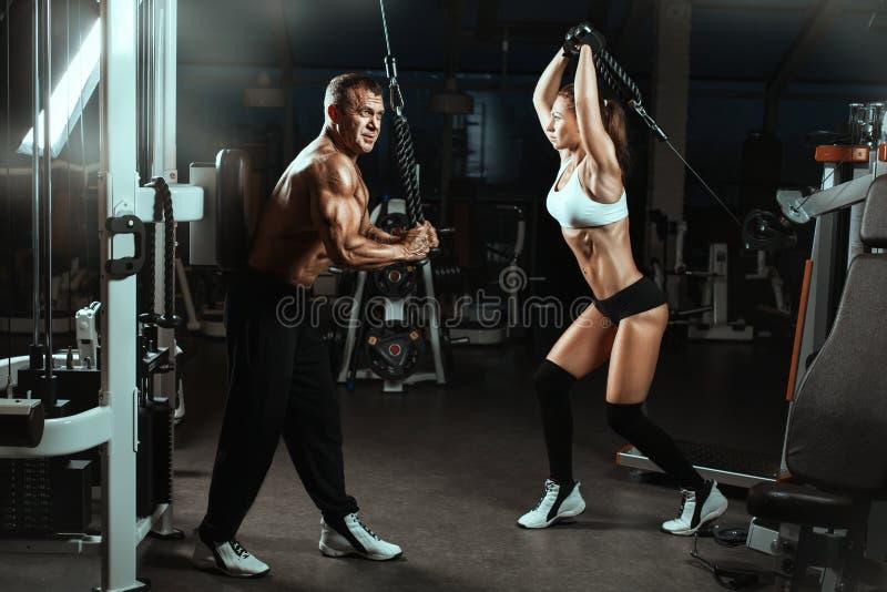Equipaggi e muscoli preparati una donna nella palestra fotografia stock