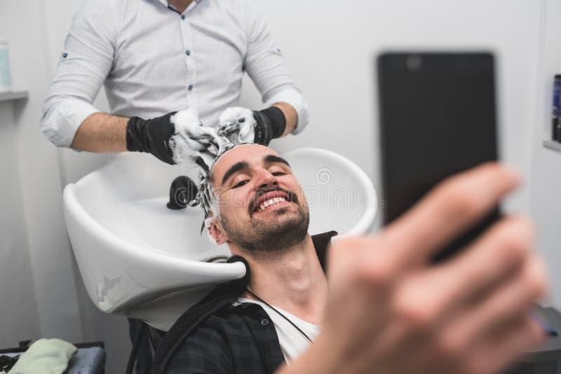 Equipaggi fare i suoi lavare capelli nel salone di lavoro di parrucchiere e per mezzo del telefono fotografia stock libera da diritti