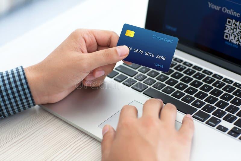Equipaggi fare la spesa online con la carta di credito sul computer portatile fotografia stock libera da diritti
