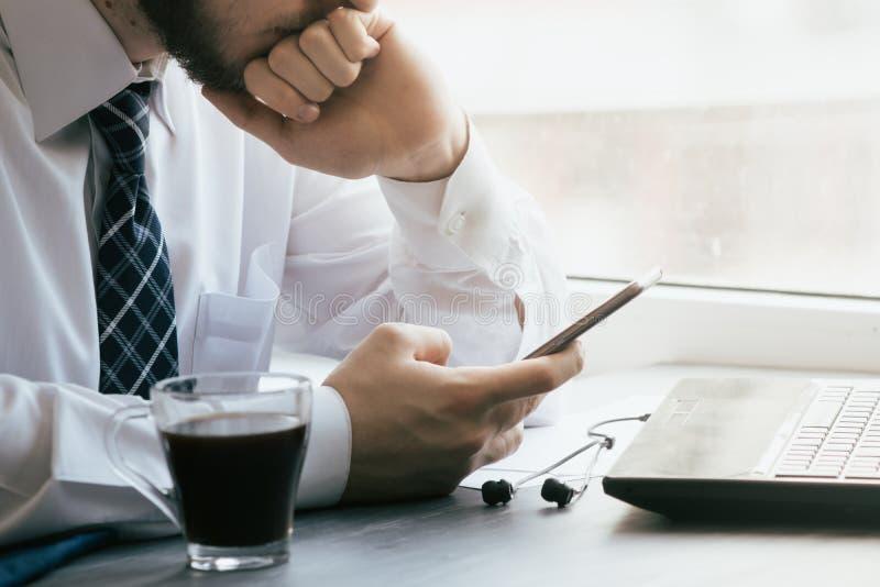 Equipaggi gli sms che mandano un sms facendo uso del app sullo Smart Phone alla notte in città Mani fotografie stock libere da diritti