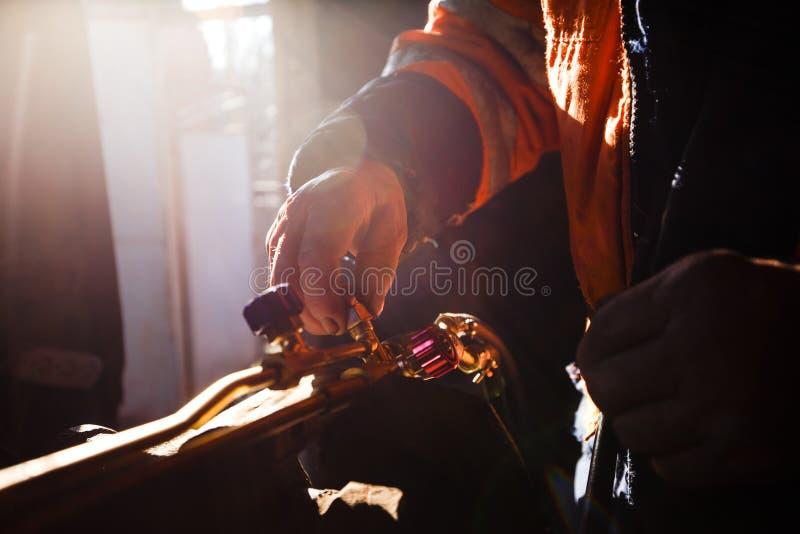 Equipaggi gli strumenti del propano della torcia dell'acetilene di ossi di pulizia per il taglio del metallo nella sua officina fotografia stock libera da diritti