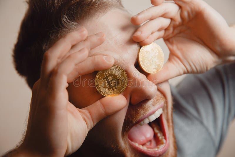 Equipaggi i morsi una moneta di oro con i suoi denti immagine stock libera da diritti