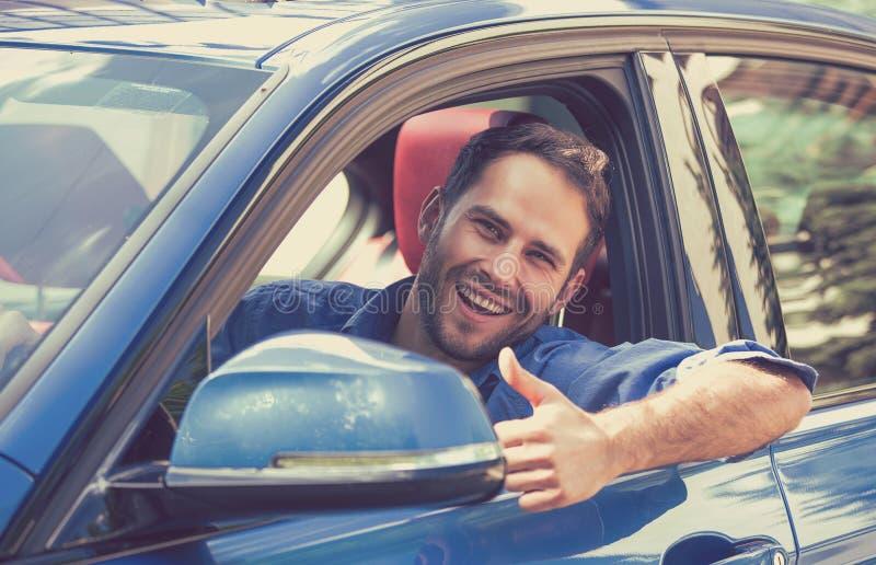 Equipaggi i pollici di mostra sorridenti felici dell'autista su che conducono l'automobile sportiva fotografia stock libera da diritti