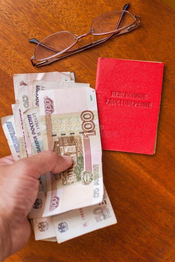 Equipaggi i soldi della tenuta della mano del ` s, i vetri ed il certificato di pensione su una traduzione superficie-inglese di  fotografia stock