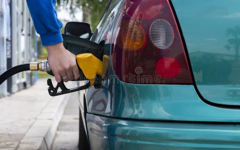 Equipaggi il combustibile di riempimento della benzina nell'ugello della holding dell'automobile immagine stock libera da diritti