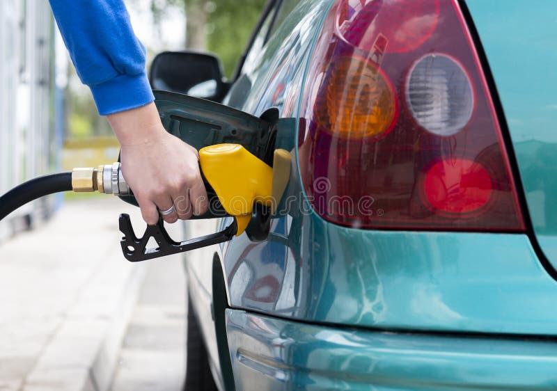 Equipaggi il combustibile di riempimento della benzina nell'ugello della holding dell'automobile fotografia stock libera da diritti