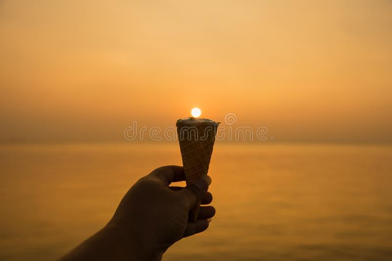 Equipaggi il cono del gelato alla vaniglia della tenuta della mano alle sedere dorate del tramonto di ora immagine stock libera da diritti