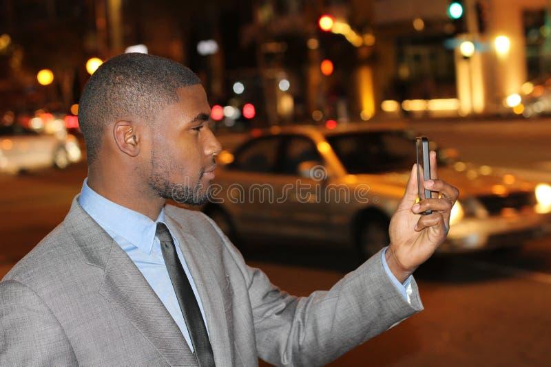 Equipaggi il controllo del suo telefono nelle vie della città immagini stock
