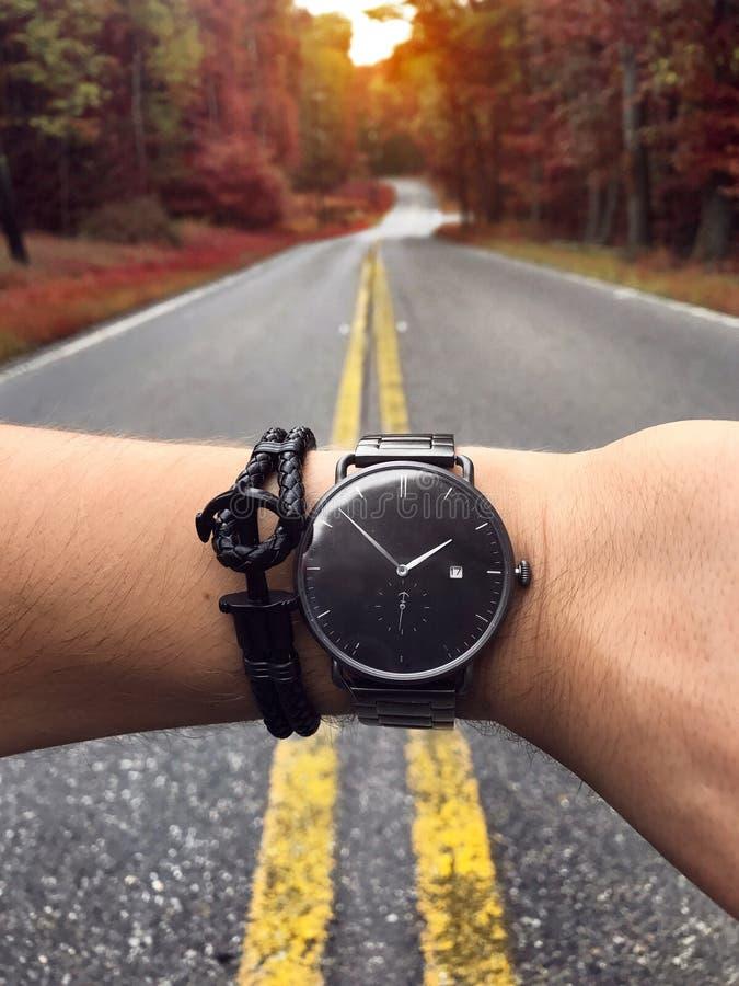 Equipaggi il controllo del tempo sull'orologio alla moda al sentiero forestale scenico fotografia stock libera da diritti