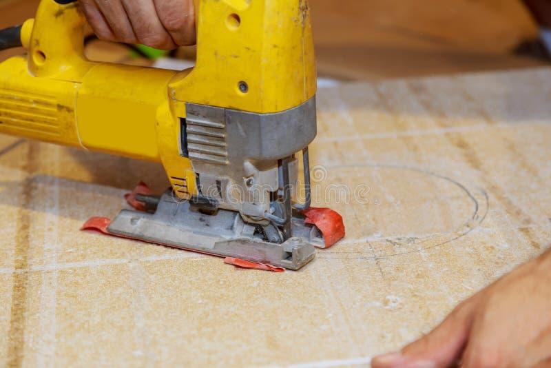 Equipaggi il costruttore del carpentiere che lavora con il puzzle ed il legno elettrici immagini stock