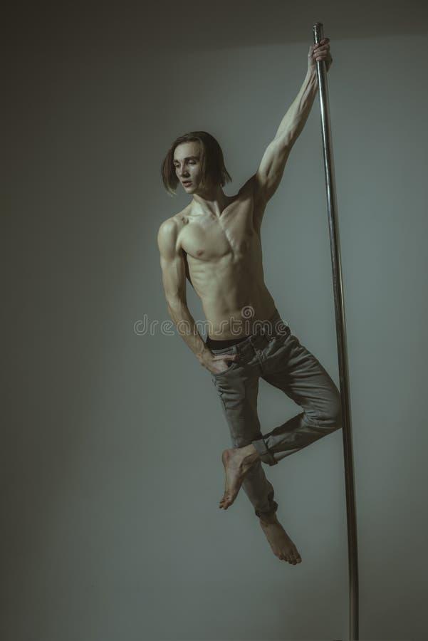 Equipaggi il dancing al palo in uno studio di forma fisica - risolvere del ballerino di balletto - allungamento del ballerino di  immagine stock