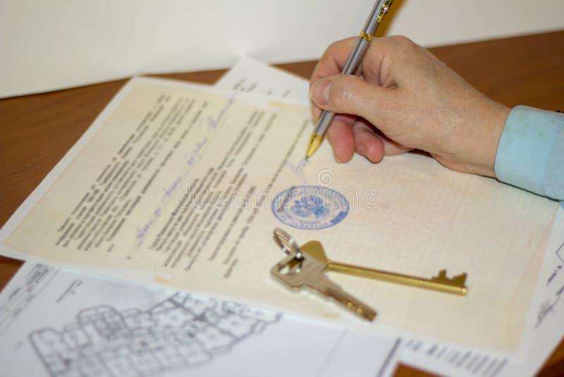 Equipaggi il documento di firma con la penna sull'acquisto e sulla vendita dell'appartamento immagine stock libera da diritti