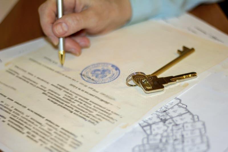 equipaggi il documento di firma con la penna sulla vendita dell'appartamento fotografie stock