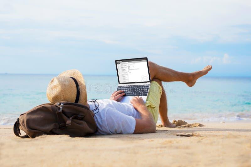 Equipaggi il email della lettura sul computer portatile mentre si rilassano sulla spiaggia immagini stock libere da diritti