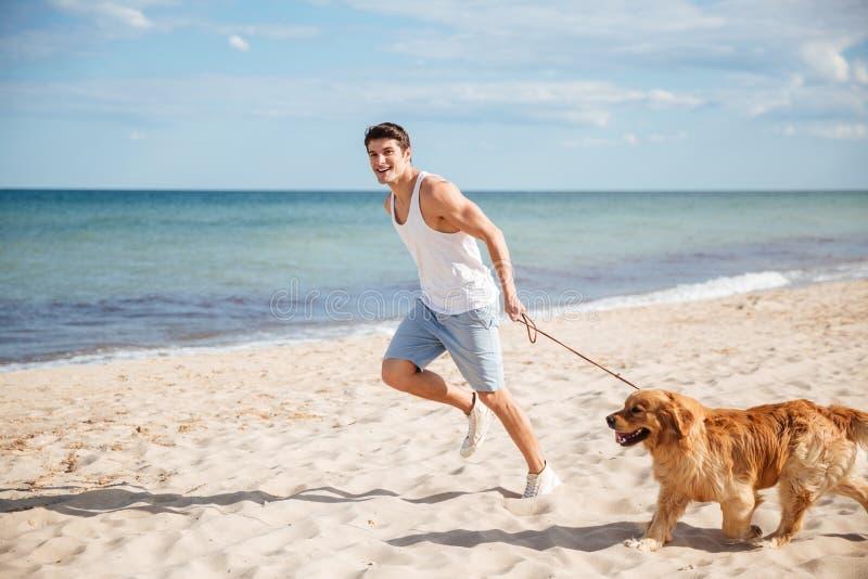 Equipaggi il funzionamento con il suo cane sulla spiaggia immagini stock libere da diritti