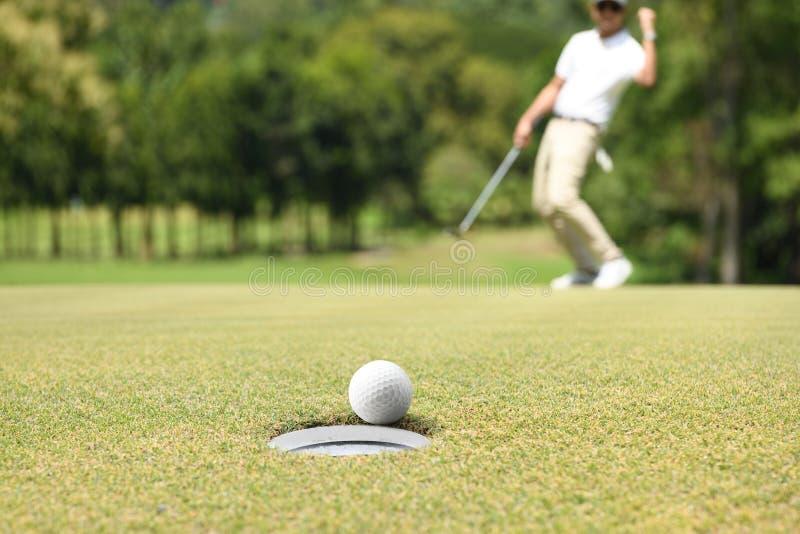 Equipaggi il giocatore di golf che incoraggia dopo una palla da golf su un verde del golf fotografia stock libera da diritti