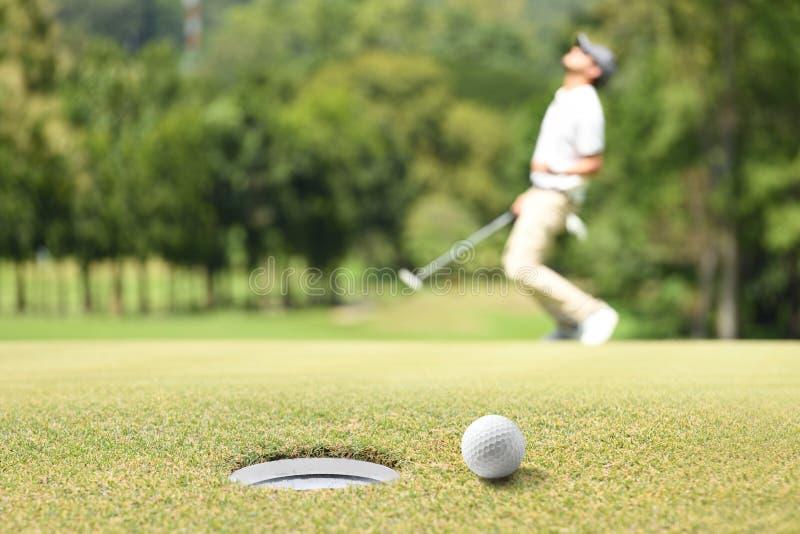 Equipaggi il giocatore di golf che incoraggia dopo una palla da golf su un verde del golf fotografie stock