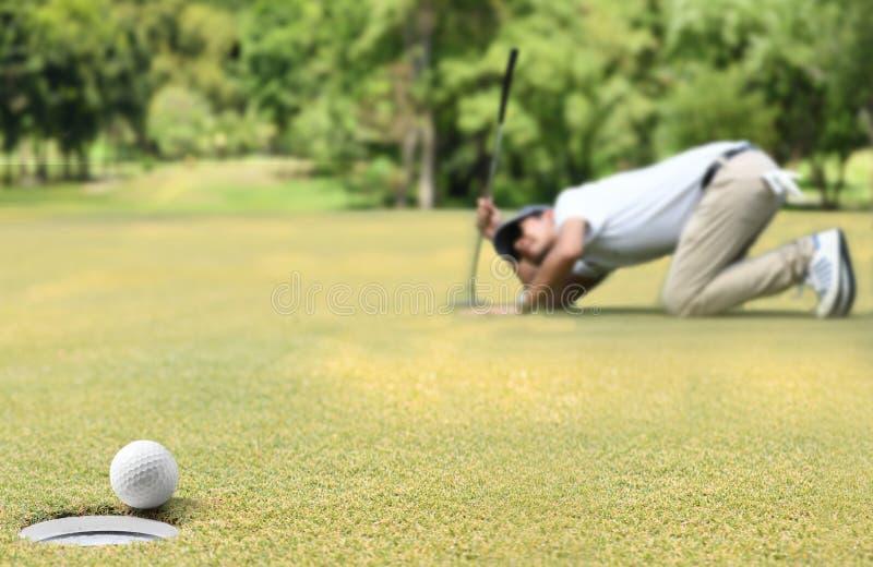 Equipaggi il giocatore di golf che incoraggia dopo una palla da golf su un verde del golf immagine stock libera da diritti