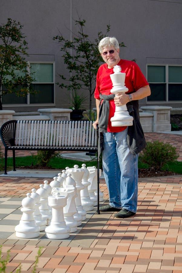 Equipaggi il gioco degli scacchi con un insieme di scacchi all'aperto fotografia stock libera da diritti