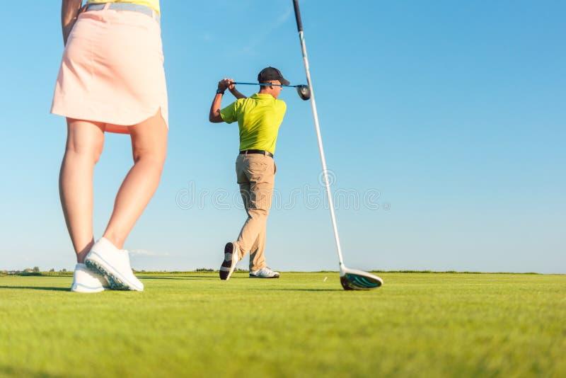 Equipaggi il gioco del golf professionale con il suo partner durante la gara a buche fotografia stock
