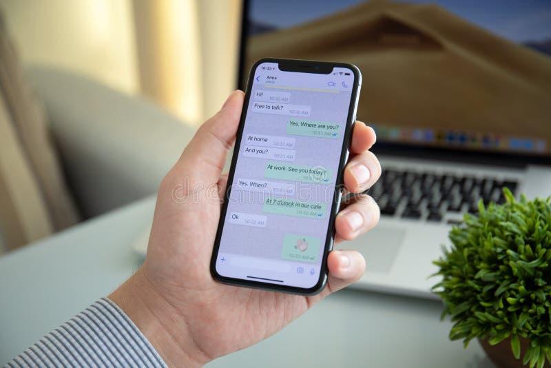 Equipaggi il iPhone X della tenuta con servizio WhatsApp della rete sociale immagini stock libere da diritti