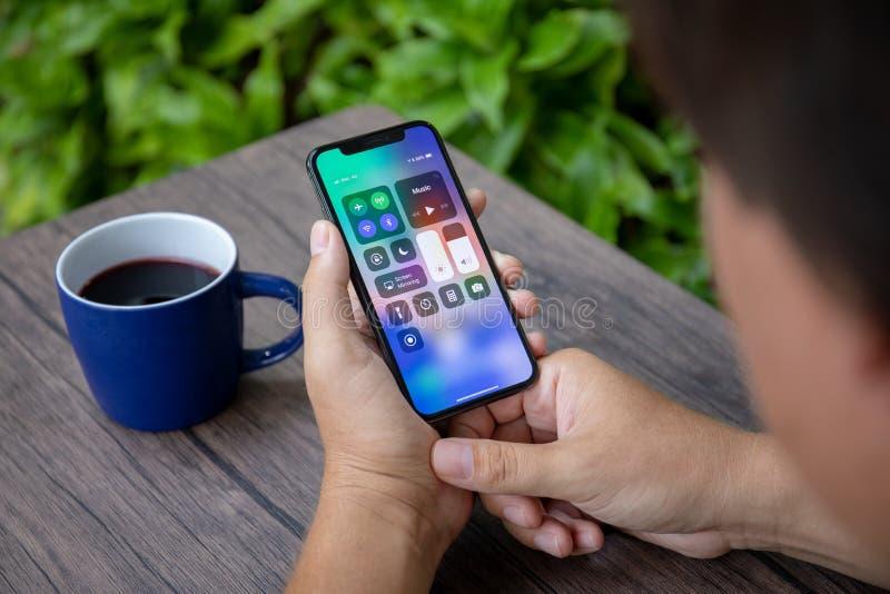 Equipaggi il iPhone X della tenuta della mano con lo schermo domestico Control Center fotografia stock libera da diritti
