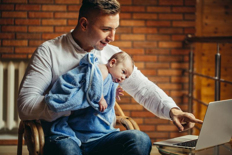Equipaggi il lavoro allo scrittorio a casa con il computer portatile, tenendo i babys svegli, esaminanti lo schermo fotografie stock