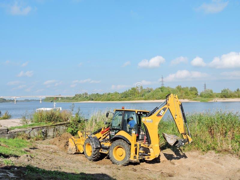 Equipaggi il lavoro con il trattore vicino al fiume, Lituania fotografie stock libere da diritti