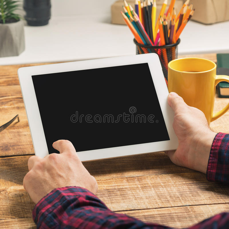 Equipaggi il lavoro facendo uso del computer della compressa che si siede nel suo Ministero degli Interni fotografie stock libere da diritti
