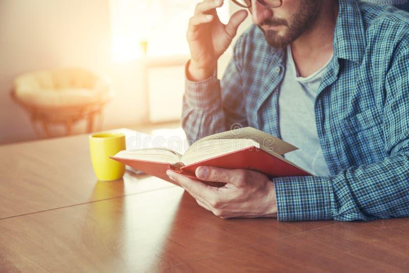 Equipaggi il libro di lettura con la tazza di tè o di caffè fotografie stock