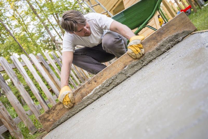 Equipaggi il livellamento del cemento in un cortile a casa facendo uso di un pla di legno fotografie stock