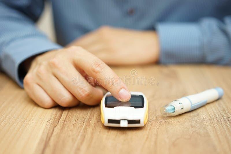 Equipaggi il livello del glucosio di prova con un glucometer digitale fotografie stock libere da diritti