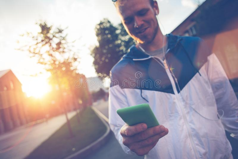 Equipaggi il messaggio di battitura a macchina sul suo telefono cellulare e la camminata sulla via fotografia stock libera da diritti