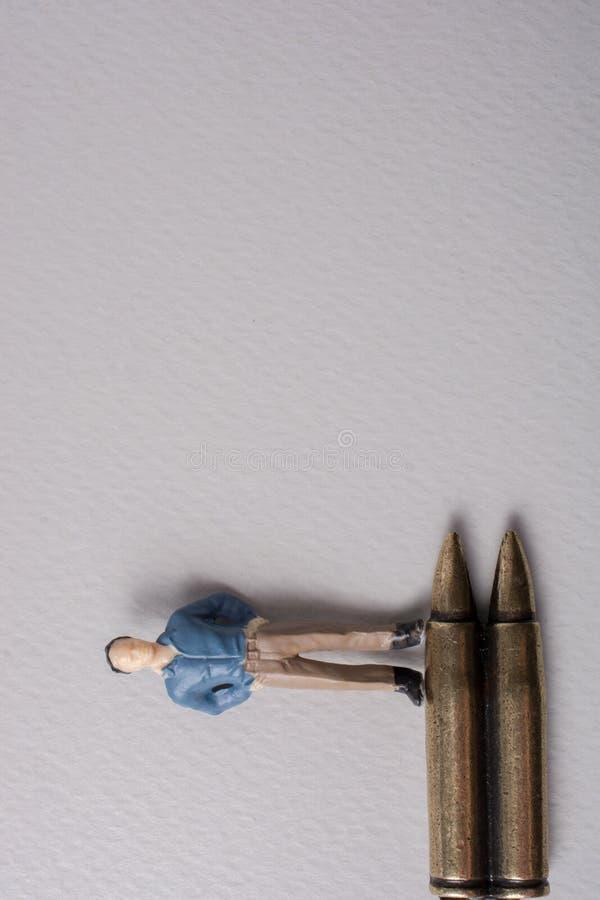 Equipaggi il modello e la pallottola della figurina come concettuale contro la guerra fotografia stock