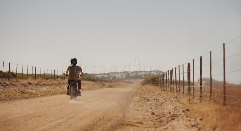 Equipaggi il motociclo di guida su una strada campestre immagini stock