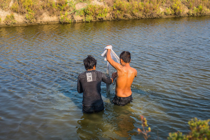 Equipaggi il pescatore locale dell'Asia che lavora vicino fuso una rete immagine stock libera da diritti