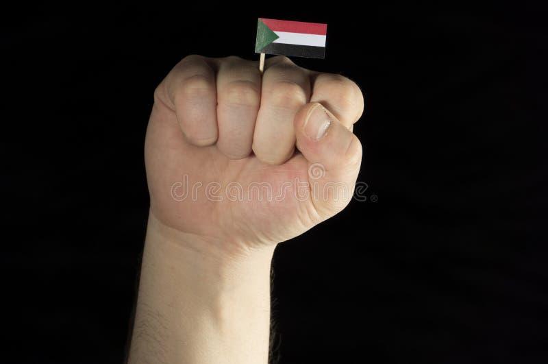 Equipaggi il pugno della mano con la bandiera del sudanese isolata sul nero immagini stock