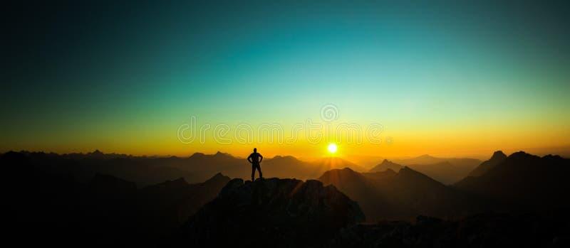 Equipaggi il raggiungimento della sommità che gode della libertà e che guarda verso l'alba delle montagne immagine stock libera da diritti
