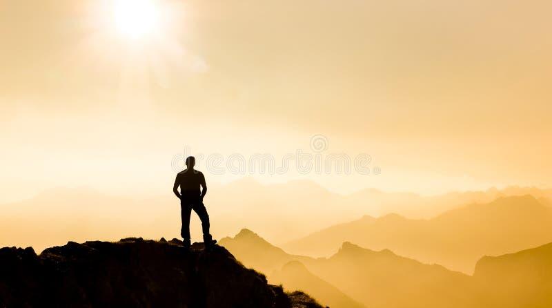 Equipaggi il raggiungimento della sommità che gode della libertà e che guarda verso le catene montuose fotografia stock